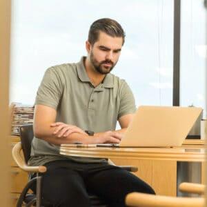 Zdjęcie ilustrujące mężczyznę pracującego nalaptopie